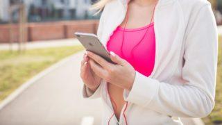 Apple製スマホで音楽を聴く女性